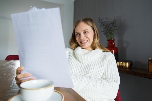 Señora alegre en el suéter blanco que examina los papeles en casa