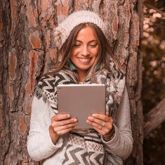 Señora alegre con tableta cerca de árbol