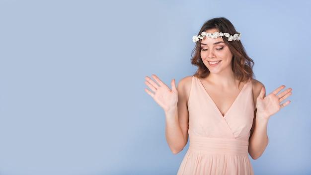 Señora apasionada feliz en vestido con flores blancas en la cabeza