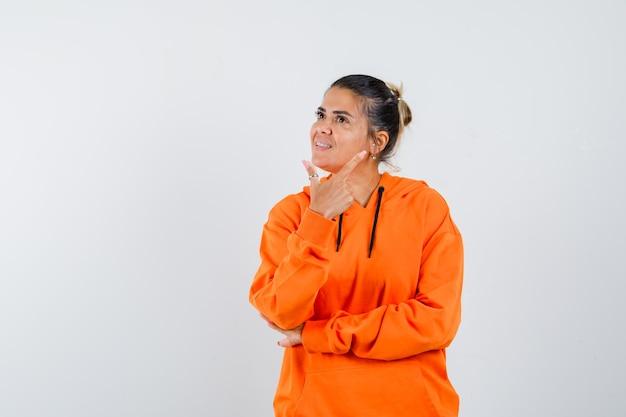 Señora apuntando a la esquina superior derecha en sudadera con capucha naranja y mirando feliz