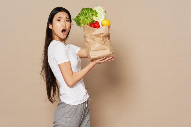 Señora asiática con una bolsa de papel con verduras