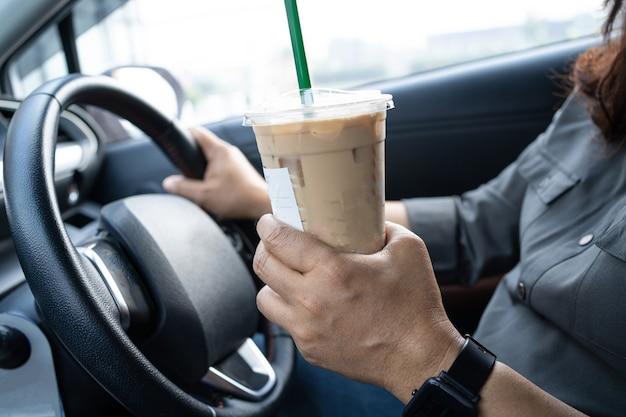 Señora asiática con café helado en coche peligroso y riesgo de accidente.
