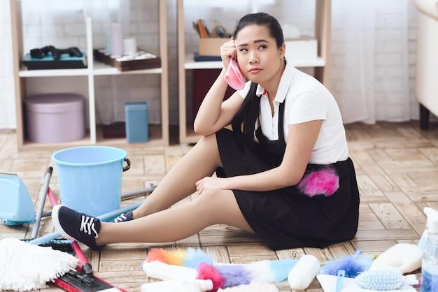 Señora asiática cansada de la camarera que se sienta en piso