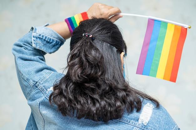 Señora asiática con chaqueta de mezclilla azul o camisa de mezclilla y sosteniendo la bandera de colores del arco iris.