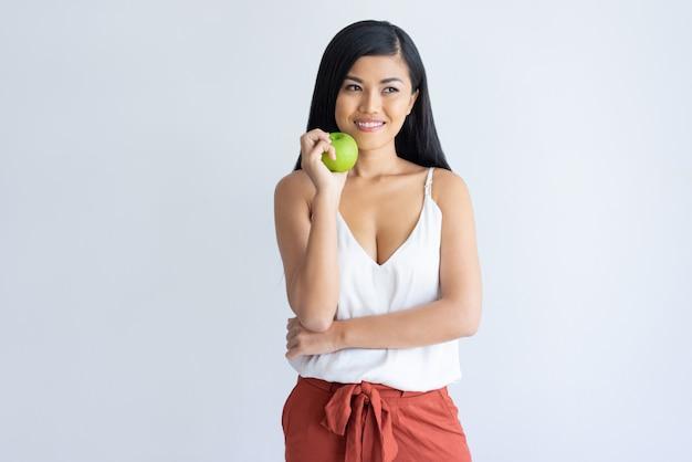 Señora asiática creativa sonriente que sostiene la manzana y que mira a un lado