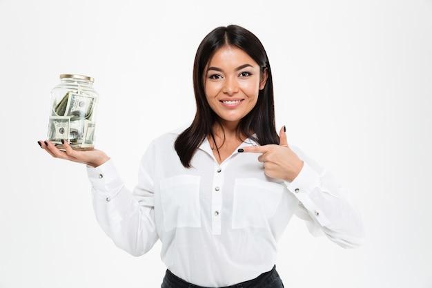 Señora asiática feliz que sostiene el tarro con el dinero que muestra los pulgares para arriba.