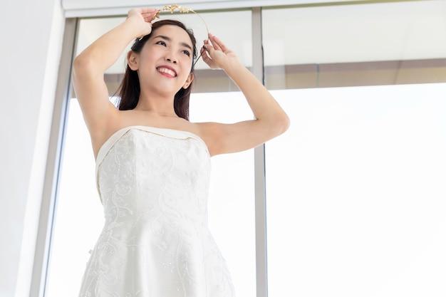 Señora asiática hermosa que elige el vestido en una tienda de la boda.