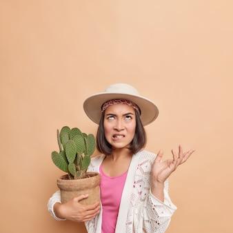La señora asiática irritada muerde los labios levanta la palma y mira con enojo por encima de la mano sostiene el cactus en maceta usa un abrigo de punto blanco fedora posa contra la pared marrón, copia el espacio para su promoción