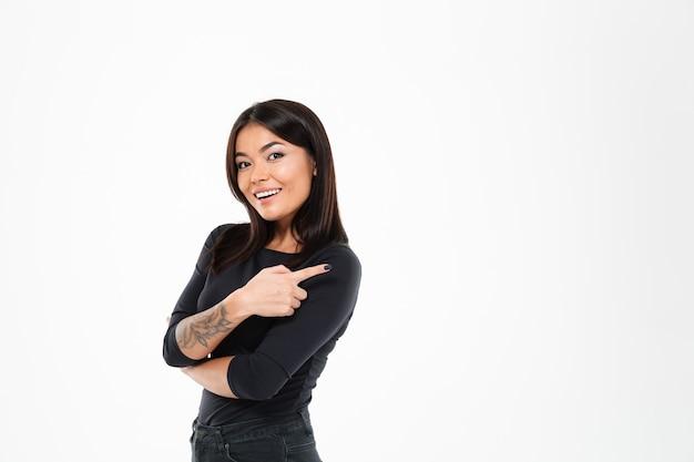 Señora asiática joven alegre que señala al copyspace.