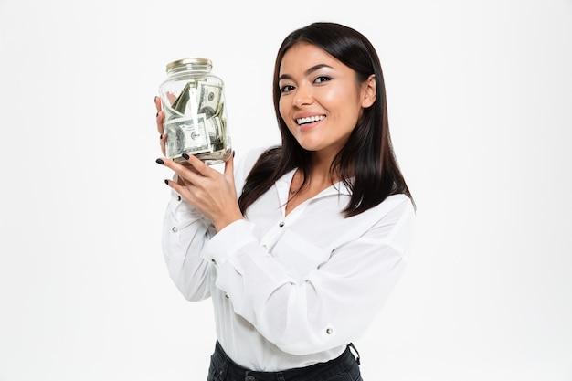 Señora asiática joven feliz que sostiene el tarro con el dinero.