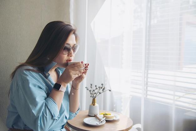 Señora asiática joven feliz del retrato en cafetería