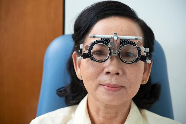 Señora asiática madura con marco de lente de prueba durante el examen de la vista