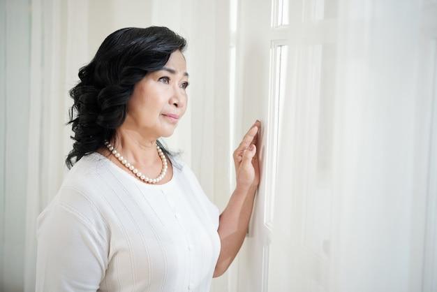 Señora asiática madura de pie junto a la ventana y mirando