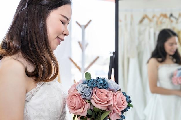 Señora asiática está mirando en el espejo y sonriendo mientras elige vestidos de novia en la tienda.