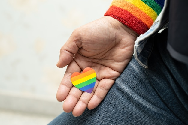 Señora asiática que sostiene el símbolo del corazón de la bandera del color del arco iris del mes del orgullo lgbt