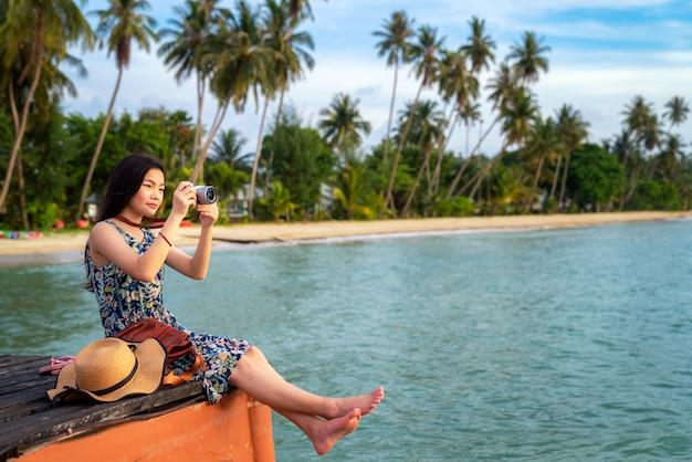 Señora asiática relajarse y tomar fotos en el puente arbolado