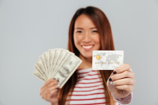 Señora asiática sobre la pared gris con dinero y tarjeta de crédito.