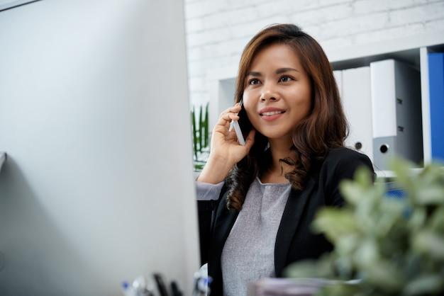 Señora asiática sonriente del negocio que sostiene smartphone al oído y que mira la pantalla de computadora