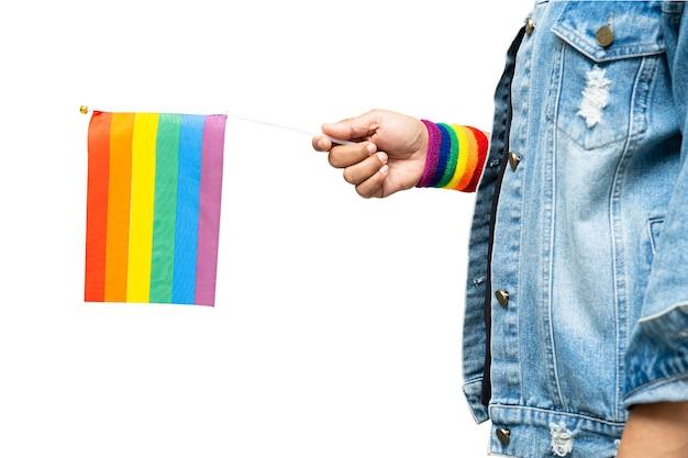 Señora asiática sosteniendo el símbolo de la bandera del color del arco iris de lgbt