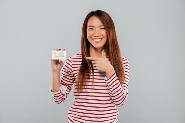 Señora asiática con tarjeta de crédito y apuntando.
