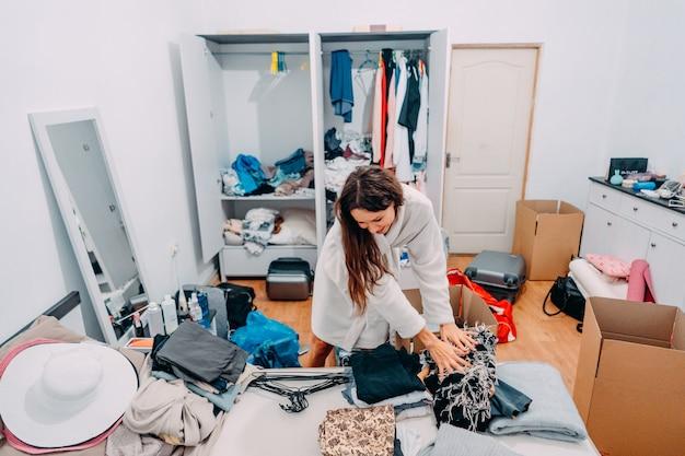 Señora de aspecto agradable dentro de la habitación moderna del apartamento prepararse para el viaje