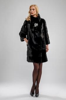 Señora atractiva en abrigo de piel negro.