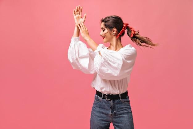 Señora atractiva en blusa blanca aplaudiendo sobre fondo rosa. bella dama con una venda roja en el pelo y con lápiz labial brillante en poses de blusa.