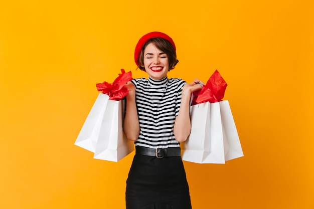 Señora atractiva en boina francesa sosteniendo bolsas de tienda