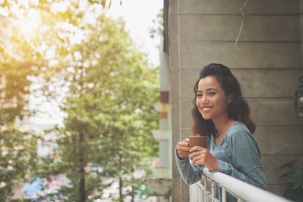 Señora atractiva joven sonriendo a la cámara de pie en el balcón y relajarse con una taza de té