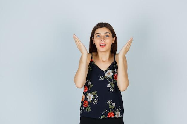 Señora atractiva levantando las palmas de las manos cerca de la cabeza en blusa y mirando asombrado, vista frontal.