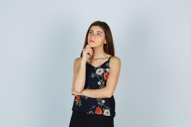 Señora atractiva manteniendo la mano debajo de la barbilla mientras mira hacia arriba en la blusa y se ve pensativa. vista frontal.