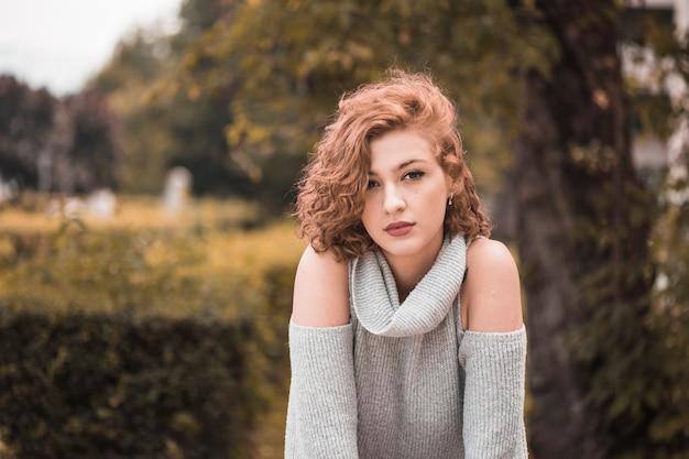 Señora atractiva con el pelo corto y rizado en el jardín público