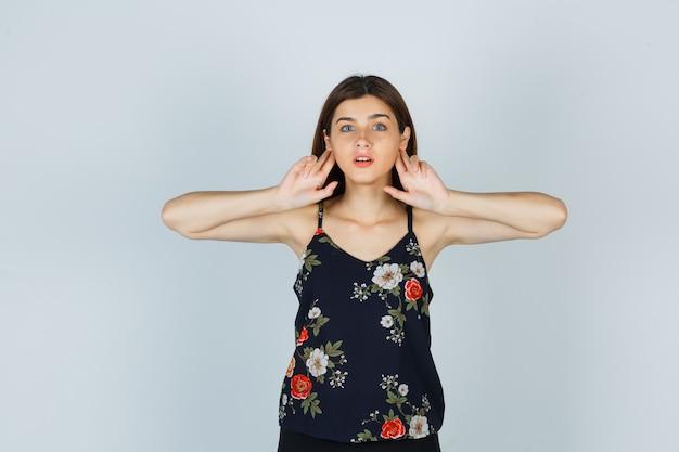 Señora atractiva sosteniendo los dedos detrás de las orejas en blusa y mirando enfocado. vista frontal.