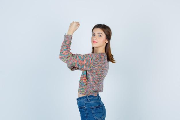 Señora atractiva en suéter, jeans mostrando sus músculos y buscando confianza.