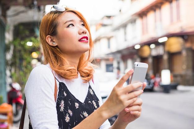 Señora atractiva con teléfono inteligente en la calle
