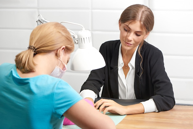 Señora atractiva en traje de oficina recibiendo manicura y disfrutando el procedimiento en el salón.