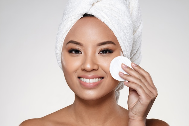 Señora bastante alegre con una toalla en la cabeza limpiando su cara