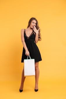 Señora bastante joven en el vestido negro que sostiene bolsos de compras.