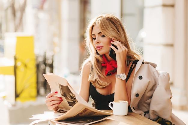 Señora bastante ocupada posando en el restaurante al aire libre con el periódico leyéndolo con interés en el fondo borroso