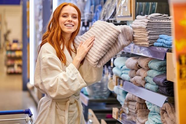 Señora en bata de baño de compras, compra una toalla, disfrutando de la suavidad de la toalla nueva cerca de los estantes