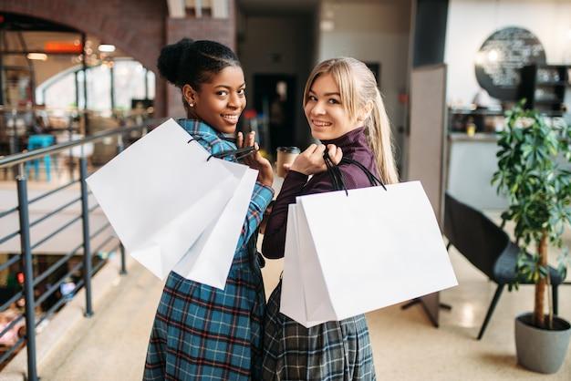 Señora blanca y negra con bolsas de compras en el centro comercial. adictos a las compras en la tienda de ropa, compras, compradoras en la tienda