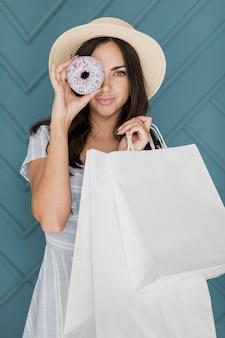Señora con bolsas de compras cubriendo su ojo con una rosquilla