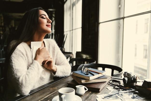 La señora bonita abraza fotos viejas que se sientan en la tabla en café