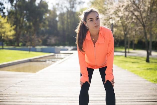Señora bonita deportiva que se inclina en rodillas y que se relaja en parque de la ciudad