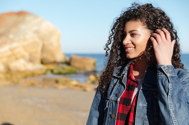 Señora bonita joven africana que camina al aire libre en la playa.