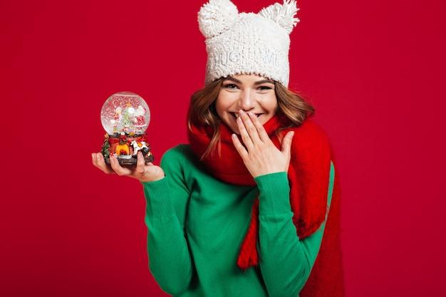 Señora bonita joven con sombrero y bufanda con juguete de navidad