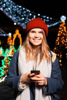 Señora bonita joven está sonriendo a la cámara mientras sostiene su teléfono.