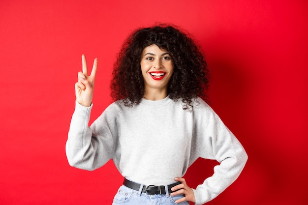 Señora bonita joven en sudadera que muestra el número dos, haciendo un pedido y sonriendo, de pie sobre fondo rojo.
