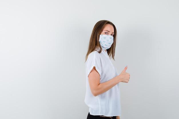 Señora bonita mostrando los pulgares para arriba mientras usa máscara