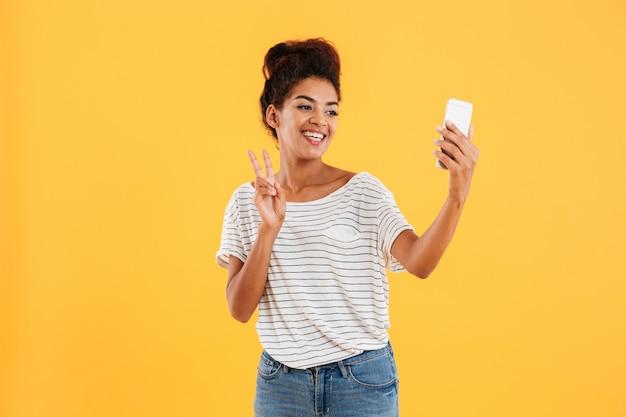 Señora bonita positiva haciendo selfie en teléfono aislado